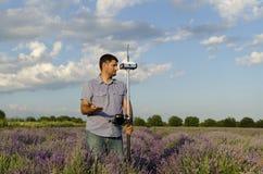 Landfeldmesser, das auf einem Lavendelgebiet und einer Wartehilfe arbeitet Stockfoto