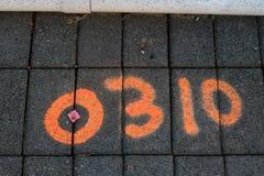 Landfeldmesserkennzeichen auf Fliese gepflastertem Bürgersteig Stockfotos