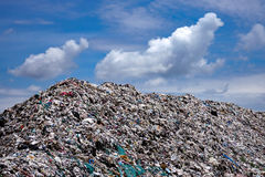 Landfill with blue sky and cumulus clouds Royalty Free Stock Photos