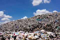 Landfill with blue sky and cumulus clouds Stock Photos