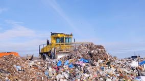 A landfill compactor bulldozer levels down a pile of trash. Water, air contamination concept. A landfill compator breaks down and moves a large pile of trash stock footage