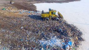 A landfill buldozer moves on a garbage pile edge. A landfill compactor in a circular view on an edge of a garbage pile stock footage