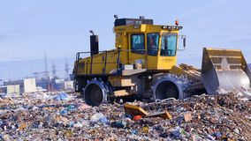 A landfill compactor moves with a raised blade at a city landfill. Waste, garbage, dump, rubbish 4K. A landfill compactor with a raised bucket drives away to stock video footage
