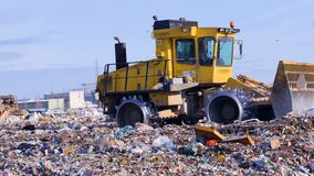 A landfill compactor working at landfill. Waste, garbage, dump, rubbish 4K. A landfill compactor with spiked wheels enters and leaves a camera shot stock footage