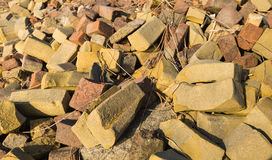 Landfill of failed bricks from a brick factory. Closeup of an overgrown trash heap with the colorful misshapen bricks from a brick factory Royalty Free Stock Photography