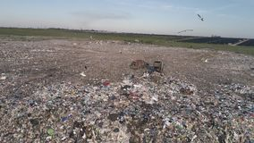 Landfill near solar panels, aerial view on workers unloading garbage from trucks and flying seagulls over large rubbish stock footage