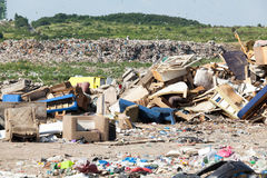 Landfill. Old furniture at the garbage dump. Old furniture at the garbage dump in focus, nature and blue sky in the background Stock Image