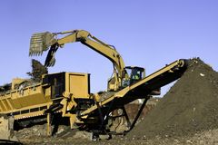 Landfill Screener. Frontend loader dumps landfill into a screener to separate solid waste from good soil which is transported by conveyor belt to preserve Royalty Free Stock Photos