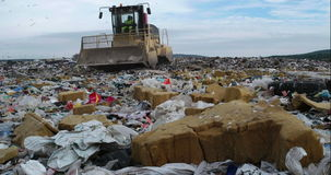 Landfill site. Truck flattening household garbage on a landfill waste site stock footage