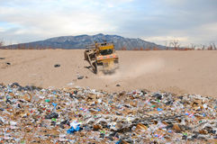 Landfill and tractor in desert. Scenic view of yellow tractor in Albuquerque desert, pile of trash in foreground, New Mexico, U.S.A Royalty Free Stock Image