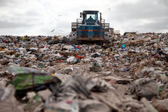 Landfill truck. Garbage piles up in landfill site each day while truck covers it with sand for sanitary purpose Stock Images