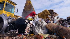 A landfill truck moving big and small garbage at landfill. A low angle on a landfill compactor moving small and large waste stock footage