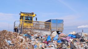 A landfill truck works near a garbage truck. A landfill compactor in close view near a sill garbage truck stock video footage