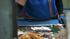 Process of garbage sorting for recycle, close up. Landfill workers sort trash, removing paper from a conveyor. Landfill workers sort trash, removing paper from stock video footage