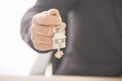Landgoedagent die huissleutels op een zilveren gevormd huis geven keychain Stock Afbeelding