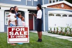 Landgoedagent en familie buiten huis met een ï ¿ ½ voor saleï¿ teken ½ royalty-vrije stock afbeeldingen