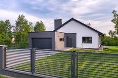 Landhaus mit Zaun und Garage lizenzfreie stockbilder