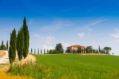 Landhaus mit Zypresse in Toskana, Italien lizenzfreie stockbilder