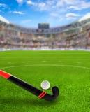 Landhockeyarena med pinnen och boll på fält royaltyfri foto