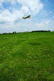 Landing. A piper pawnee plane landing in a green airfield Royalty Free Stock Photo