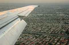 Landing. The wing over the town while the plane is landing royalty free stock image