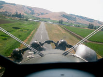 Landing. Biplane landing on a small town one lane airport view through the windshield Royalty Free Stock Photo