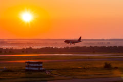 Landing aircraft in the morning crimson. Landing airplane in the morning crimson Stock Photography