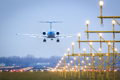 Landing aircraft over runway. Rear view of airliner over landing lights about to land on runway Stock Photography