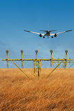 A landing airplane flying over a field Stock Images