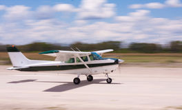 Landing airplane with motion blur. Small airplane landing on a gravel air strip with motion blur to convey movement Royalty Free Stock Photo