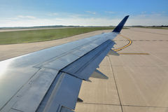 Landing. Airplane wing before flight, and airport runway, shown as travel concept, departure, start of trip, or industrial of transportation Royalty Free Stock Photos