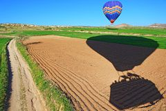 Hot air balloons landing in spring fields Cappadocia Turkey. Landing hot air balloons in green fields in Cappadocia/Kapadokia Turkey.Cappadocia has unreal Stock Image