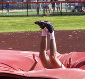 Landing into the mat during high jump. A male high school track and field athlete is engulfed by red matts as he lands on them during a high jump competition stock image