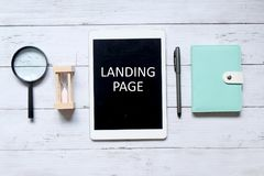 Landing page. Top view of magnifying glass,hourglass,pen,notebook, and tablet computer written & x27; LANDING PAGE& x27; on white wooden backrgound Stock Photography