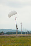 Landing parachutist on the power line. Royalty Free Stock Photo
