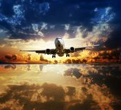 Landing plane flying over water surface reflecting sky Royalty Free Stock Images