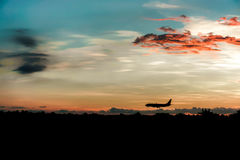 Landing plane when warm sunset Stock Image