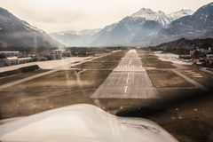 Landing. A propeller airplane landing in Sion airport in the middle of the snow covered Alps mountain range in Valais, Switzerland Stock Photos