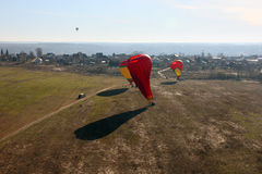 Landing red and yellow air balloons on the field in clear weathe Royalty Free Stock Image