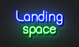 Landing space neon sign on brick wall background. Stock Photo