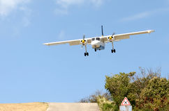 Landing at St. Barth airport, Caribbean. The arrival descent is extremely steep over the hilltop traffic circle Stock Photos