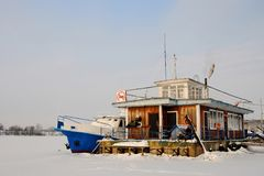 Landing stage frozen into ice. Landing stage and a boat are frozen into ice, Volga river, Uglich, Yaroslavl region, Russia Royalty Free Stock Images
