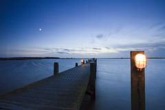 Landing stage with a little light at sunset. Stock Image