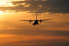 Landing at sunset. Turbo-prop airplane is approaching Rwy at sunset Royalty Free Stock Image