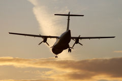 Landing at sunset. Turbo-prop airplane approaching Rwy Royalty Free Stock Photography
