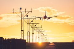 Landing at the sunset. Airplane landing on the airport runway at the sunset. Prague, Czech Republic Stock Images