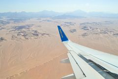 Landing and turning the plane over the desert. Altitude view of the desert, mountains sunlight. Hurghada, Egypt - May 14th, 2018: View from the porthole on the royalty free stock photography