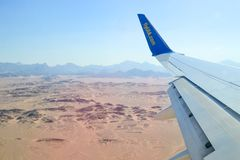 Landing and turning the plane over the desert. Altitude view of the desert, mountains sunlight. Hurghada, Egypt - May 14th, 2018: View from the porthole on the royalty free stock photo