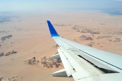 Landing and turning the plane over the desert. View from the porthole on the wing of the plane with the fenders raised during landing at the Egyptian airport stock image