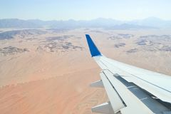 Landing and turning the plane over the desert. View from the porthole on the wing of the plane with the flaps down during landing at the Egyptian airport stock photo